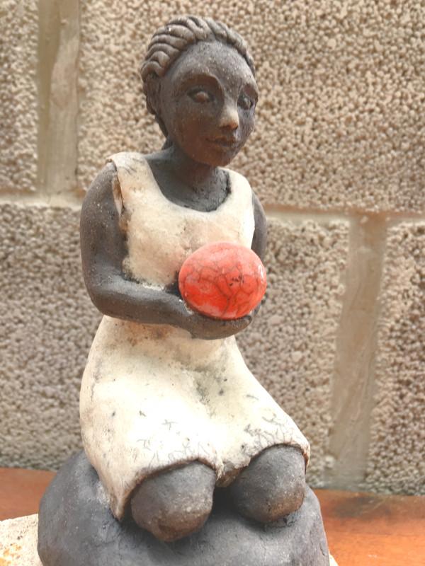 Flicka med röd boll keramikskulptur i rakuteknik